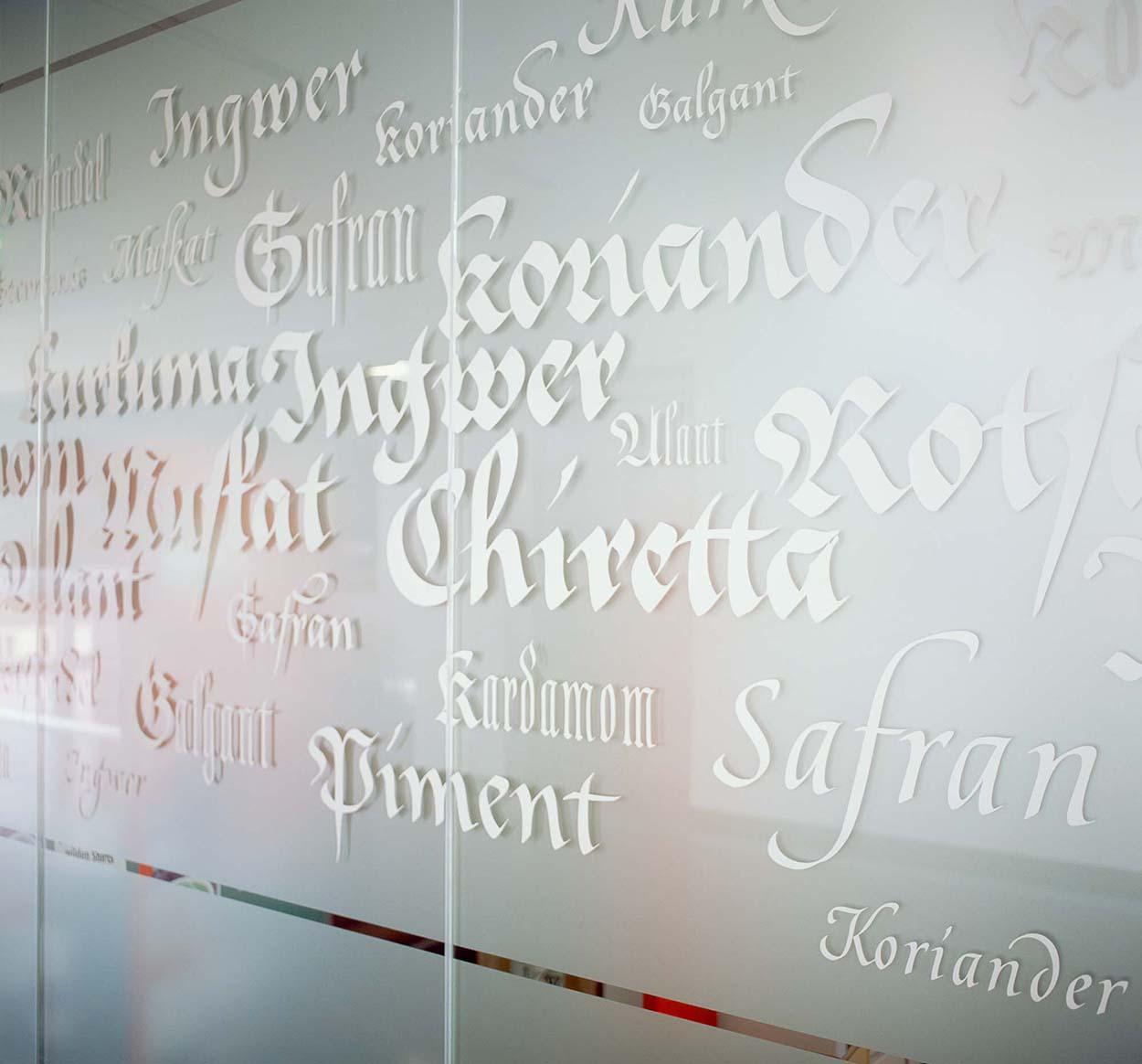 Glaswand mit KraeuternamenKalligrafie