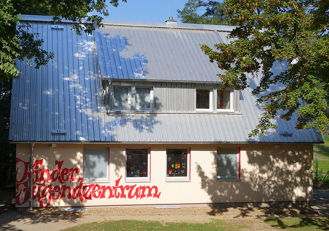 Hausfassade zwischen Baeumen